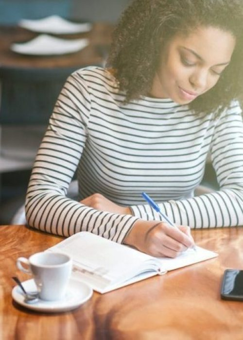 Attractive young woman is sitting at table in cafe. She is writing her ideas in notebook with inspiration